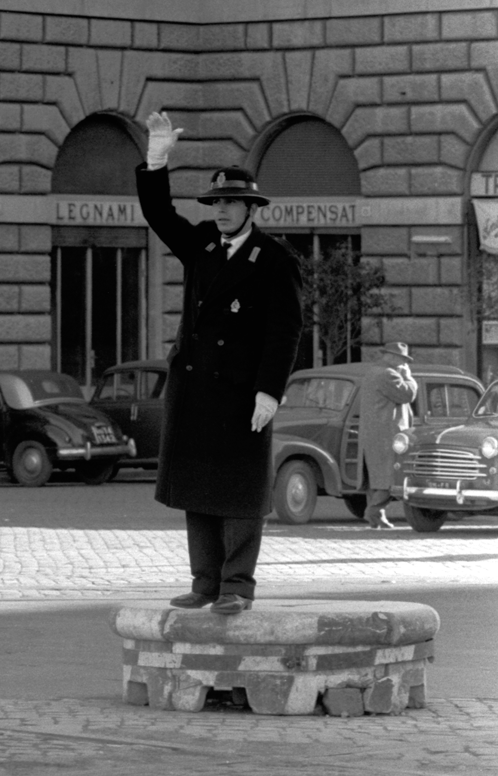 Policeman guiding traffic at crossroad standing on raised platform