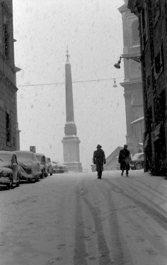 Two men walking down street with Rome obelisk in background