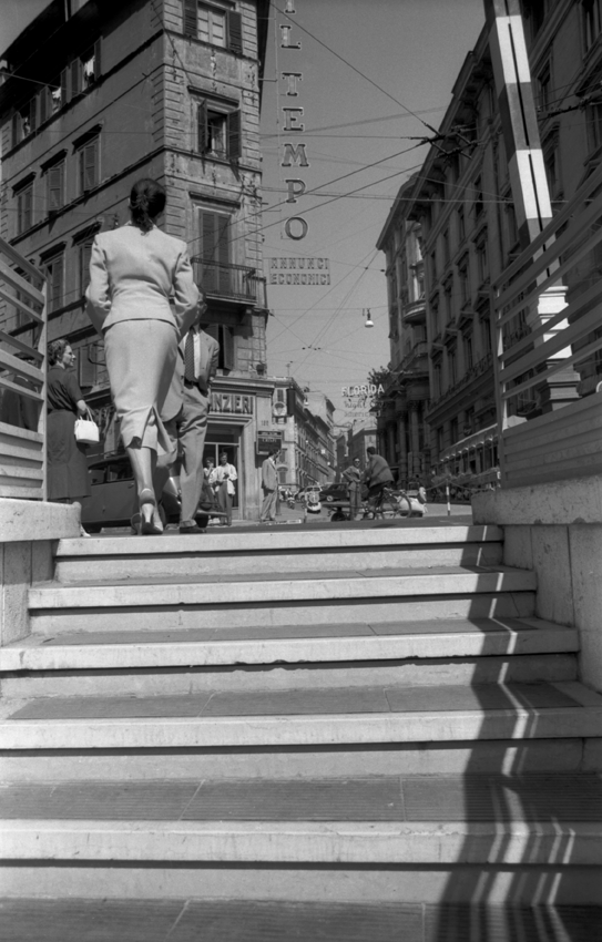 A woman walking away at the top of a staircase leading onto the main road
